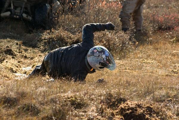 Участник соревнований падает, помогая вытащить квадроцикл из болота